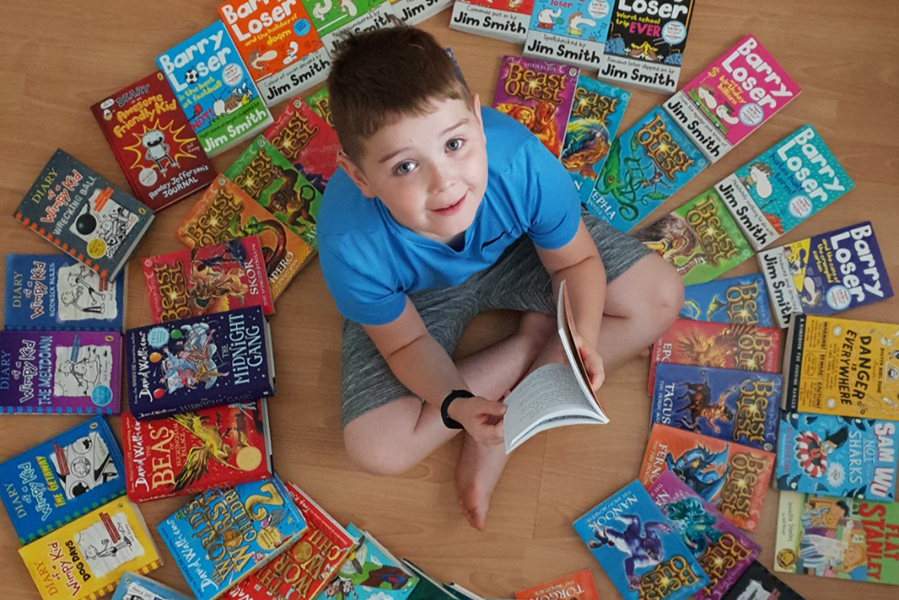 Josh Cullen, a pupil at Hollybush Primary School in Derry sitting on the floor surrounded by books
