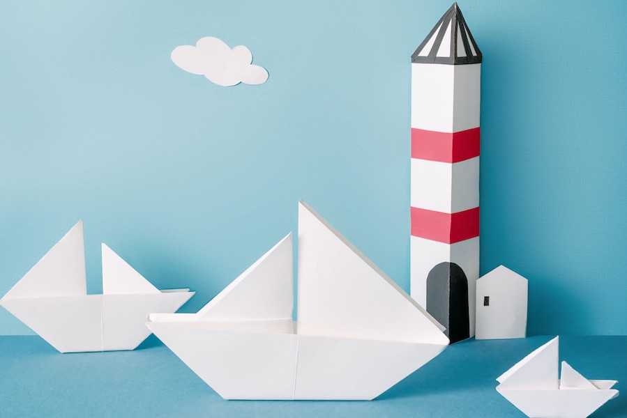Origami boats sail in front of a cardboard lighthouse