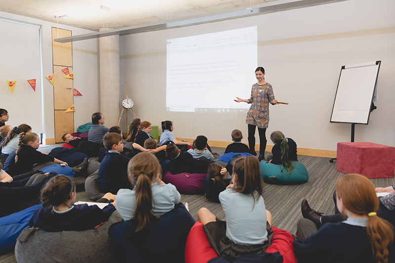 A Fighting Words volunteer leading a writing workshop in front of a class of children who are reclining on beanbags